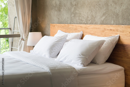 Valokuva  White pillows on the bed in loft style bedroom.