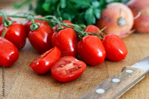 Grape tomatoes on vine with one halved tomato on wood chopping board next to a kitchen knife.