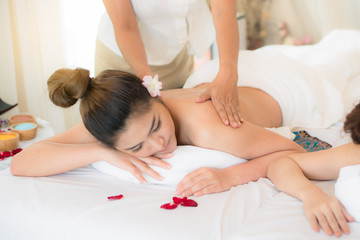 Obraz na płótnie Canvas Relaxation oil massage spa salon. Beautiful young asian woman lying down on the bed relax in spa salon with massage Selective focus on hand.