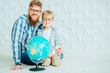 Father and son in eyeglasses looking at camera with globe at home and having fun. Full body? copy space.