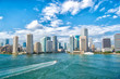canvas print picture - Aerial view of Miami skyscrapers with blue cloudy sky,white boat sailing next to Miami downtown