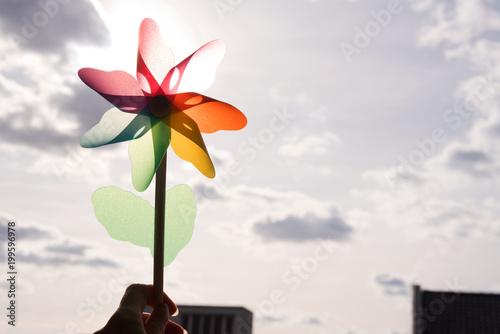 Fotografia, Obraz  Rainbow coloured pinwheel held up against cloudy sky with sun shining though