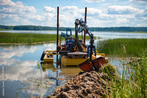 Cleaning the bottom of the lake with a dredge Fototapet