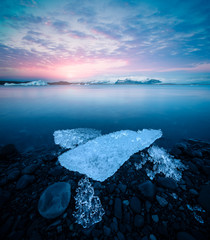 Jokulsarlon glacier lagoon with ice chunks and mountains at beautiful sunset in Iceland