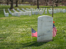 Lonely White Grave Stone With US Flag At Arlington National Cemetery, Virginia