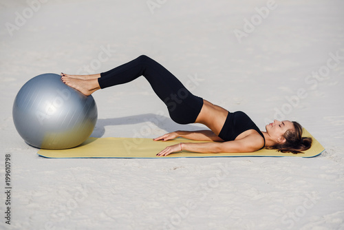 Beautiful fitness girl doing pilates exercises with fit ball on the beach. Sport and healthy lifestyle concept.