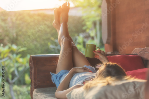 Foto  Girl enjoying morning coffee on the porch.