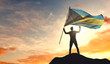 Bahamas flag being waved by a man celebrating success at the top of a mountain. 3D Rendering