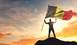 Belgium flag being waved by a man celebrating success at the top of a mountain. 3D Rendering