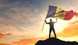 Andorra flag being waved by a man celebrating success at the top of a mountain. 3D Rendering