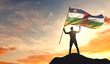 Central African Republic flag being waved by a man celebrating success at the top of a mountain. 3D Rendering