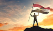 Egypt flag being waved by a man celebrating success at the top of a mountain. 3D Rendering