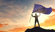 European Union flag being waved by a man celebrating success at the top of a mountain. 3D Rendering