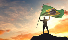 Brazil Flag Being Waved By A Man Celebrating Success At The Top Of A Mountain. 3D Rendering