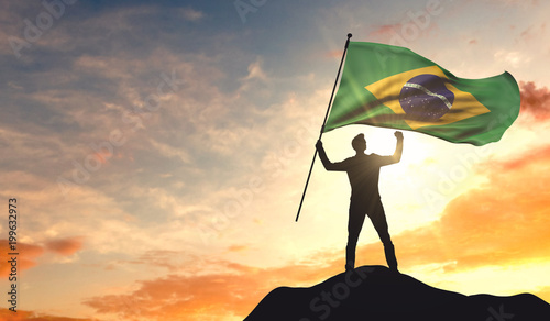Brazil flag being waved by a man celebrating success at the top of a mountain Canvas