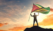 Guyana flag being waved by a man celebrating success at the top of a mountain. 3D Rendering