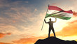 Hungary flag being waved by a man celebrating success at the top of a mountain. 3D Rendering