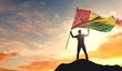Guinea Bissau flag being waved by a man celebrating success at the top of a mountain. 3D Rendering