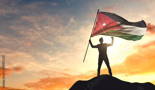 Valokuvatapetti Jordan flag being waved by a man celebrating success at the top of a mountain