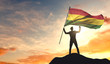Bolivia flag being waved by a man celebrating success at the top of a mountain. 3D Rendering