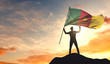 Cameroon flag being waved by a man celebrating success at the top of a mountain. 3D Rendering