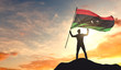 Libya flag being waved by a man celebrating success at the top of a mountain. 3D Rendering