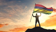 Mauritius flag being waved by a man celebrating success at the top of a mountain. 3D Rendering