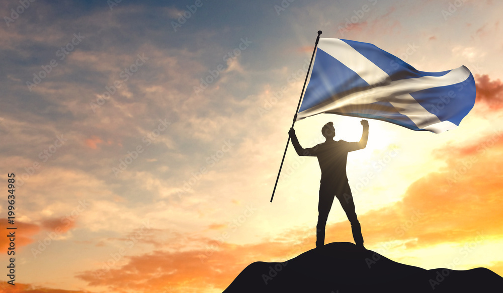 Fototapeta Scotland flag being waved by a man celebrating success at the top of a mountain. 3D Rendering
