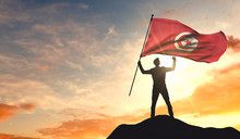 Tunisia Flag Being Waved By A Man Celebrating Success At The Top Of A Mountain. 3D Rendering