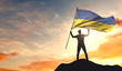 Ukraine flag being waved by a man celebrating success at the top of a mountain. 3D Rendering