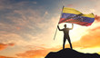 Venezuela flag being waved by a man celebrating success at the top of a mountain. 3D Rendering