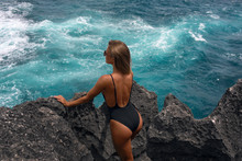 Girl Standing On Rocks Looking At Blue Raging Ocean