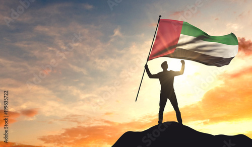 Fotografie, Obraz  United Arab Emirates flag being waved by a man celebrating success at the top of a mountain