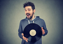 Excited Hipster Man With Vinyl Record Looking At Camera