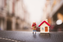 Miniature People, Woman Traveler Standing With Mini House Using As Business And Tourism Concept - Vintage Filter