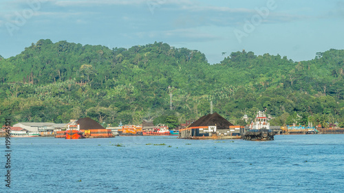 tugboats pull heavy load barge of black coal in Mahakam river, Borneo, Indonesia Tapéta, Fotótapéta