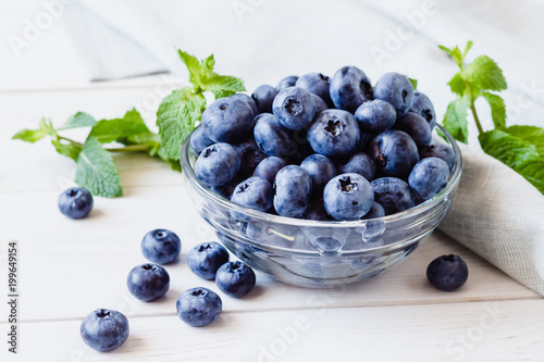 Ripe blueberries in a glass bowl and mint on a light table. Wallpaper Mural