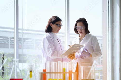 Young female scientist standing with teacher in lab worker making medical research in modern laboratory.