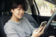 Young asian woman in casual wear driving a car, using smartphone and smiling. Risky driving. Woman sitting in car with cell phone.