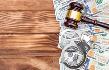 Gavel With Handcuffs And Money On The Wooden Table. Top View. Law Background.