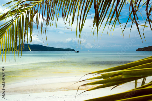 Tropical landscape of Koh Rong Samloem island with turquoise water, palm tree and mountain in the distance. Cambodia, asia.