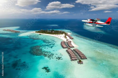 Wasserflugzeug fliegt über Malediven Insel mit türkisem Ozean und blauem Himmel