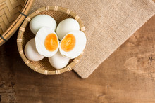 Top View Of Salted Duck Egg In Bamboo Basket On Old Wooden Table In Kitchen With Copy Space. Food Preservation Concept.
