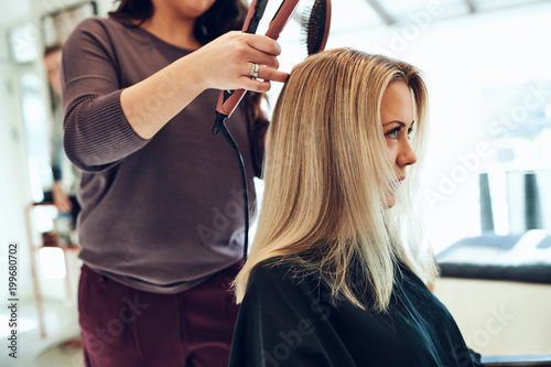 Young woman getting her hair straightened at the salon