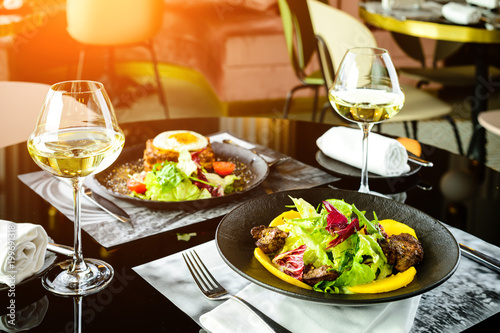 Romantic dinner at a restaurant. Appetizing dishes with meat and lettuce leaves and glasses with wine in rays of the sun