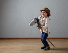 Cute Little Girl Dressed Like A Cowboy Playing With A Homemade Horse.