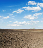 black plowed agriculture field and clouds in blue sky
