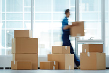 Blurred Motion Of Contemporary Worker With Packed Box Walking To New Office While Delivering It To Client