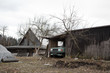Authentic yard in poor Eastern Europe. Old wooden cottage and retro vintage car is in the barn. Abandoned and desolated vehicle is partly rusty. Nostalgia of ugly fall / winter. Bare tree.