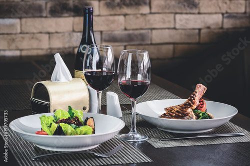 Romantic dinner in the resraurant. Two appetizing dishes and two glasses of red wine, toned image